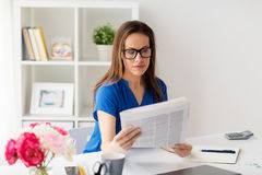 Γυναίκα στα γυαλιά που διαβάζει την εφημερίδα στο γραφείο Στοκ φωτογραφίες με δικαίωμα ελεύθερης χρήσης