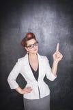Γυναίκα στα γυαλιά που παρουσιάζουν σε κάτι από το δάχτυλο Στοκ φωτογραφία με δικαίωμα ελεύθερης χρήσης