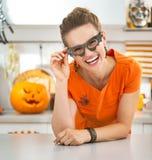 Γυναίκα στα γυαλιά ροπάλων κομμάτων στη διακοσμημένη αποκριές κουζίνα Στοκ φωτογραφία με δικαίωμα ελεύθερης χρήσης