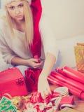 Γυναίκα στα δώρα Χριστουγέννων συσκευασίας καπέλων Santa Στοκ Εικόνα