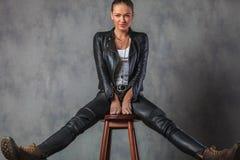 Γυναίκα στα ενδύματα και τις μπότες δέρματος που τεντώνουν τα πόδια της Στοκ φωτογραφία με δικαίωμα ελεύθερης χρήσης