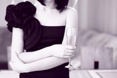 Γυναίκα στα ευτυχή κουρέλια, που κρατούν ένα ποτήρι της σαμπάνιας. inte Στοκ Φωτογραφίες