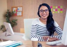 Γυναίκα στα θεάματα που κάθεται στο γραφείο της στο γραφείο Στοκ Εικόνα