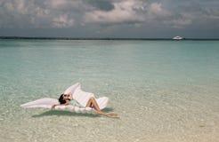 Γυναίκα στα κομψά ενδύματα παραλιών που χαλαρώνει στο νησί των Μαλδίβες Στοκ Φωτογραφία