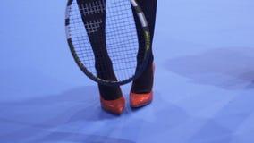 Γυναίκα στα κόκκινα παπούτσια στα υψηλά τακούνια με τη ρακέτα αντισφαίρισης φιλμ μικρού μήκους