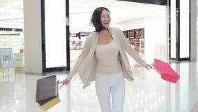 Γυναίκα στα μαλακά χρωματισμένα τζιν και σακάκι που περπατά και που περιστρέφει στη λεωφόρο φέρνοντας τις τσάντες αγορών και στα  απόθεμα βίντεο