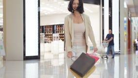 Γυναίκα στα μαλακά χρωματισμένα τζιν και σακάκι που περπατά και που περιστρέφει στη λεωφόρο φέρνοντας τις τσάντες αγορών και στα  φιλμ μικρού μήκους