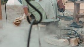 Γυναίκα στα μεσαιωνικά ενδύματα που τηγανίζουν τις τηγανίτες στον πάσσαλο φιλμ μικρού μήκους