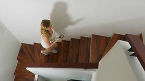Γυναίκα στα πάνινα παπούτσια που τρέχουν κατά μήκος μιας ξύλινης σκάλας φιλμ μικρού μήκους