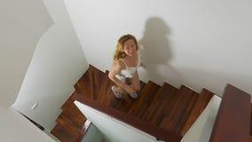Γυναίκα στα πάνινα παπούτσια που τρέχουν κατά μήκος μιας ξύλινης σκάλας απόθεμα βίντεο