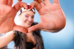 Γυναίκα στα προστατευτικά δίοπτρα σκι που κάνει τα δάχτυλα συμβόλων καρδιών Στοκ Φωτογραφίες