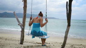Γυναίκα στα σαρόγκ που ταλαντεύονται ήπια σε μια παραλία φιλμ μικρού μήκους