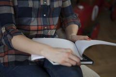 Γυναίκα στα σημειωματάρια εκμετάλλευσης πουκάμισων καρό στοκ εικόνες