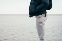 Γυναίκα στα τζιν και ένα σακάκι που στέκεται σε ένα υπόβαθρο θάλασσας στοκ φωτογραφία με δικαίωμα ελεύθερης χρήσης