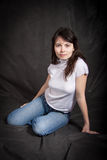 Γυναίκα στα τζιν που κάθεται στο πάτωμα Στοκ Φωτογραφία