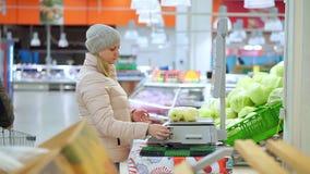 Γυναίκα στα χειμερινά ενδύματα στα ζυγίζοντας μήλα υπεραγορών στις κλίμακες Επιλέγει τον κώδικα και την αξία των φρούτων απόθεμα βίντεο