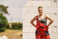 Γυναίκα στα dungarees που εργάζεται στο εργοτάξιο οικοδομής στοκ εικόνες