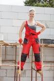 Γυναίκα στα dungarees που εργάζεται στο εργοτάξιο οικοδομής στοκ εικόνα με δικαίωμα ελεύθερης χρήσης