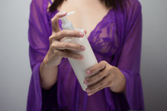 Γυναίκα στα nightdress με το λοσιόν σωμάτων στοκ εικόνα με δικαίωμα ελεύθερης χρήσης