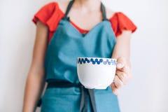 Γυναίκα στην άσπρη κούπα καφέ εκμετάλλευσης υποβάθρου στοκ εικόνα
