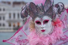 Γυναίκα στην άσπρη μάσκα και τα διακοσμητικά ρόδινα φτερά και jester ` s κοστούμι στη Βενετία καρναβάλι Στοκ φωτογραφία με δικαίωμα ελεύθερης χρήσης