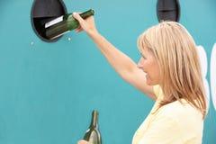 Γυναίκα στην ανακύκλωση του κέντρου στην τράπεζα μπουκαλιών Στοκ φωτογραφία με δικαίωμα ελεύθερης χρήσης
