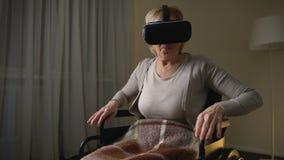 Γυναίκα στην αναπηρική καρέκλα που φορά vr την κάσκα για πρώτη φορά, ευτυχής και έκπληκτος απόθεμα βίντεο