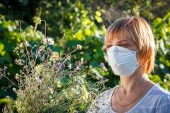 Γυναίκα στην ανθοδέσμη εκμετάλλευσης μασκών προστασίας των wildflowers και του tryi Στοκ φωτογραφία με δικαίωμα ελεύθερης χρήσης