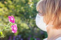 Γυναίκα στην ανθοδέσμη εκμετάλλευσης μασκών προστασίας των wildflowers και του tryi Στοκ Εικόνες