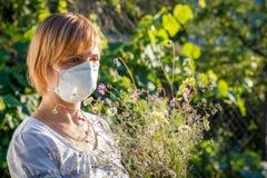 Γυναίκα στην ανθοδέσμη εκμετάλλευσης μασκών προστασίας των wildflowers και του tryi Στοκ φωτογραφίες με δικαίωμα ελεύθερης χρήσης