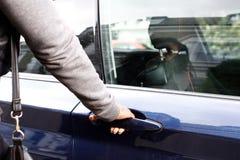 Γυναίκα στην ανοίγοντας πόρτα αυτοκινήτων σακακιών Στοκ Εικόνες