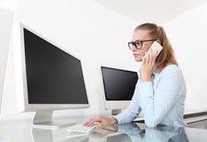 Γυναίκα στην αρχή μπροστά από τη οθόνη υπολογιστή, που μιλά επάνω Στοκ Εικόνες