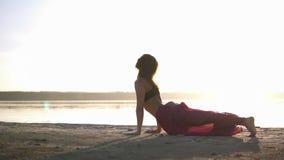 Γυναίκα στην εξάρτηση γιόγκας που κάνει τη γιόγκα σε μια παραλία και μπροστά από το νερό Το μίγμα θέτει Η γιόγκα θέτει - cobra πε φιλμ μικρού μήκους