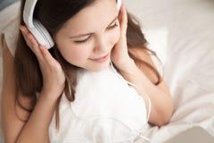 Γυναίκα στην ευχάριστη μουσική ακούσματος ακουστικών Στοκ Φωτογραφίες
