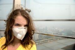 Γυναίκα στην ιατρική μάσκα ενάντια στην ατμοσφαιρική ρύπανση στοκ εικόνες