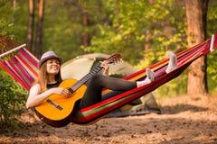 Γυναίκα στην κιθάρα παιχνιδιού καπέλων και χαλάρωση στην αιώρα στη μέση της δασικής αργής έννοιας ζωής στοκ εικόνα