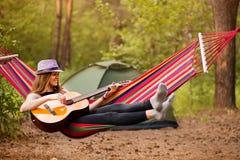 Γυναίκα στην κιθάρα παιχνιδιού καπέλων και χαλάρωση στην αιώρα στη μέση της δασικής αργής έννοιας ζωής στοκ φωτογραφίες με δικαίωμα ελεύθερης χρήσης