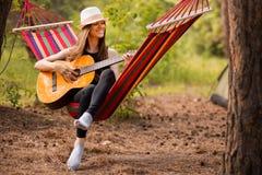 Γυναίκα στην κιθάρα παιχνιδιού καπέλων και χαλάρωση στην αιώρα στη μέση του δάσους στοκ φωτογραφία