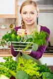 Γυναίκα στην κουζίνα που έχει τα λαχανικά που κρατούν το καλάθι αγορών Στοκ Εικόνες