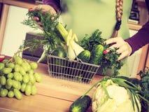 Γυναίκα στην κουζίνα που έχει τα λαχανικά που κρατούν το καλάθι αγορών Στοκ Εικόνα