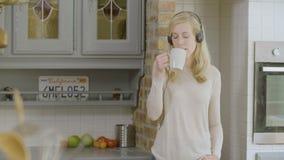 Γυναίκα στην κουζίνα που ακούει τη μουσική στα ακουστικά της που πίνουν τον καφέ απόθεμα βίντεο