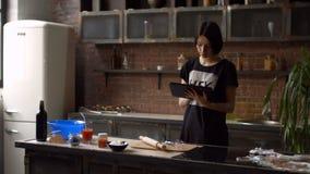 Γυναίκα στην κουζίνα που εξετάζει τη συνταγή στο PC ταμπλετών απόθεμα βίντεο