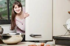 Γυναίκα στην κουζίνα που κρυφοκοιτάζει έξω από πίσω από την πόρτα ενός ανοικτού ψυγείου και που χαμογελά εξετάζοντας τη κάμερα στοκ φωτογραφίες