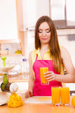 Γυναίκα στην κουζίνα που πίνει το φρέσκο χυμό από πορτοκάλι Στοκ φωτογραφία με δικαίωμα ελεύθερης χρήσης