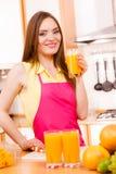 Γυναίκα στην κουζίνα που πίνει το φρέσκο χυμό από πορτοκάλι Στοκ φωτογραφίες με δικαίωμα ελεύθερης χρήσης