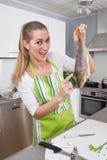 Γυναίκα στην κουζίνα που προετοιμάζει το γεύμα ψαριών με την πέρκα - χιουμοριστική Στοκ Φωτογραφίες