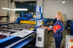 Γυναίκα στην κόκκινη εργασία κρανών ασφάλειας ως βιομηχανικό εργάτη Στοκ Εικόνες