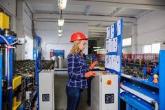 Γυναίκα στην κόκκινη εργασία κρανών ασφάλειας ως βιομηχανικό εργάτη Στοκ Φωτογραφία
