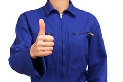 Γυναίκα στην μπλε εργασία ομοιόμορφη κάνοντας το ΕΝΤΑΞΕΙ σημάδι Στοκ εικόνα με δικαίωμα ελεύθερης χρήσης