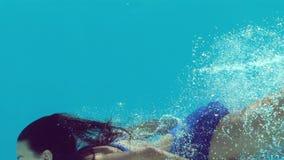 Γυναίκα στην μπλε κολύμβηση μαγιό υποβρύχια απόθεμα βίντεο